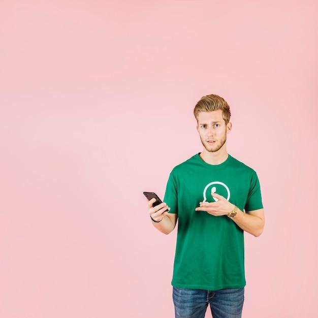 Portret van een mens die terwijl het houden van mobiele telefoon gesturing Gratis Foto