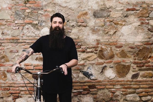 Portret van een mens met fiets die zich voor verlaten muur bevindt Gratis Foto