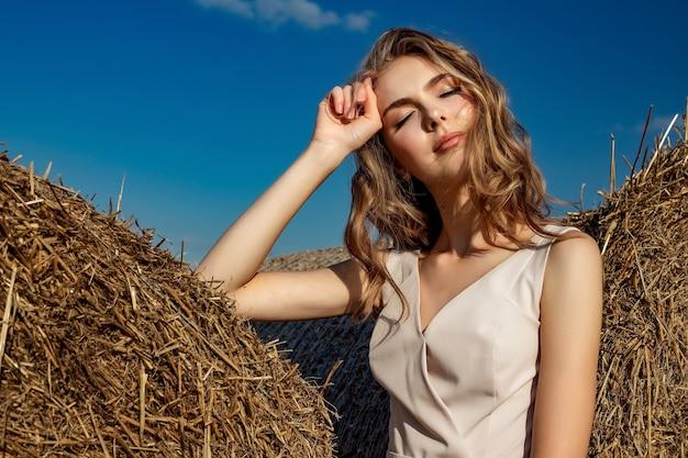 Portret van een model van het blonde jonge meisje dat zich op een zonnige dag bevindt en stelt Premium Foto