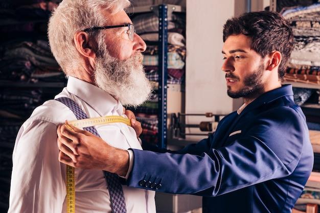Portret van een modeontwerper die de borst van zijn klant meet in zijn atelier Gratis Foto