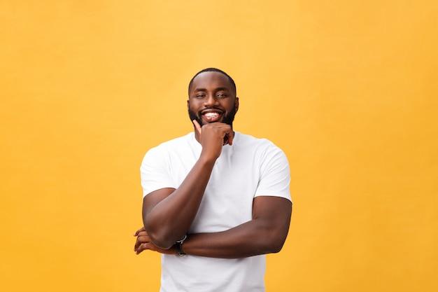 Portret van een moderne jonge zwarte man glimlachend met armen gekruist op geïsoleerde gele achtergrond Premium Foto