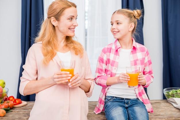 Portret van een moeder en dochter houden glas sap in de hand te kijken naar elkaar Gratis Foto