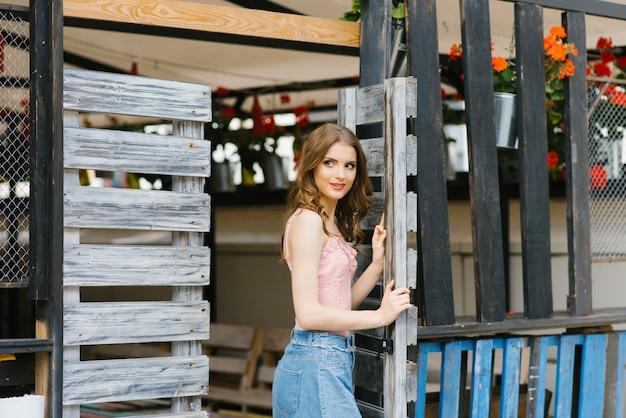 Portret van een mooi en mooi meisje dat zich in een houten poort bevindt. het concept van een nieuw leven of de voltooiing van het eerste Premium Foto