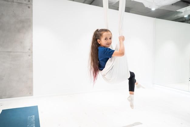 Portret van een mooi jong meisje die zich bezighouden met vlieg yoga op doeken. Gratis Foto