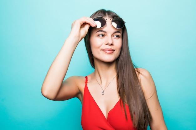 Portret van een mooi jong meisje in zonnebril op een blauwe muur Gratis Foto