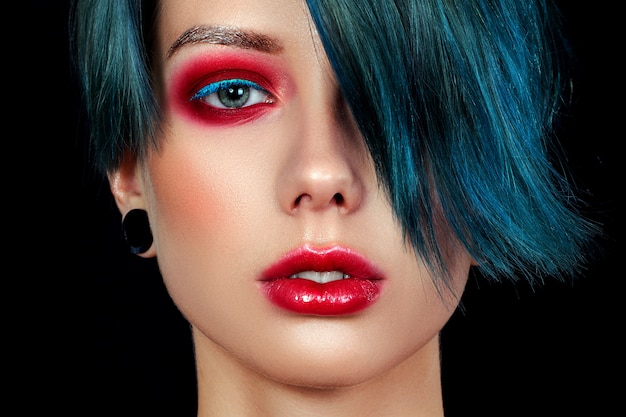 Portret van een mooi jong meisje met een professionele samenstelling, buitenissig meisje. punkmeisje met blauwe ogen, rode lippen en blauwe, groene folio's Premium Foto