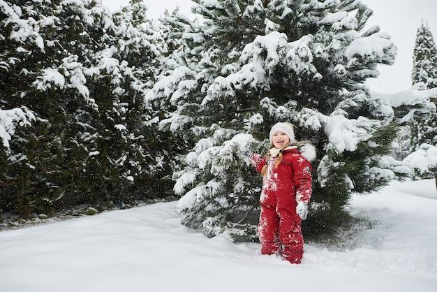Portret van een mooi kaukasisch meisje op een achtergrond van met sneeuw bedekte kerstbomen. reclame voor warme winterkleren Premium Foto