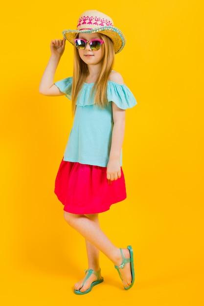 Portret van een mooi meisje in een hoed, zonnebril, zomerjurk en sandalen. Premium Foto