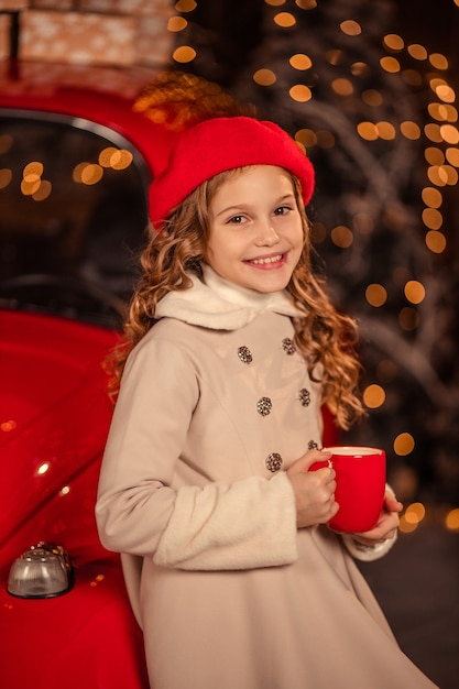 Portret van een mooi meisje in een rode baret met een mok in haar handen tegen de achtergrond van een rode new year's auto Premium Foto