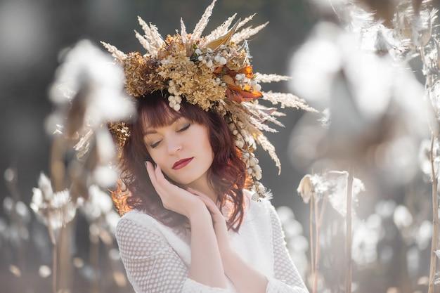 Portret van een mooi meisje in een witte vintage jurk en herfstkrans van gedroogde bloemen op het hoofd in het midden van luchtige en pluizige planten Premium Foto
