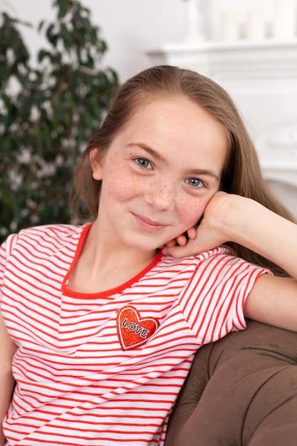 Portret van een mooi roodharigetienermeisje. leuke meisjeszitting op de bank, het glimlachen en het bekijken de camera Premium Foto