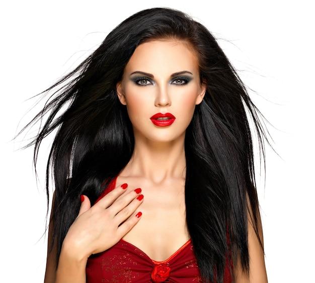 Portret van een mooie brunette vrouw met rode nagels en lippen Gratis Foto