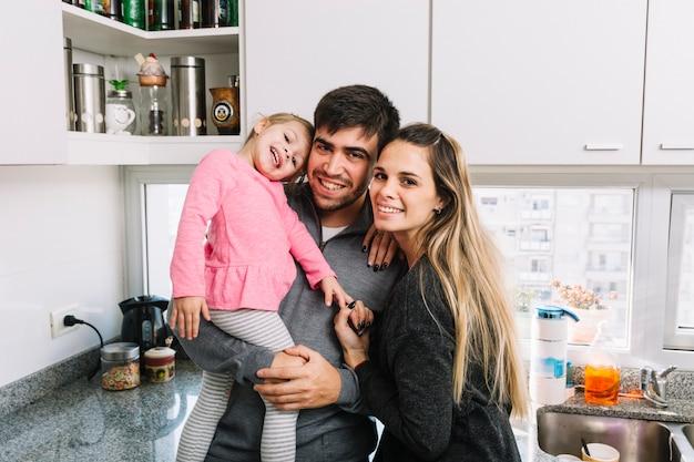 Portret van een mooie familie in de keuken Gratis Foto