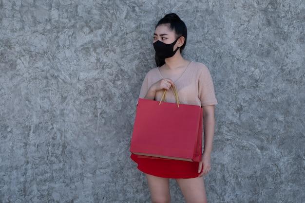 Portret van een mooie jonge aziatische vrouw, gekleed in een gezichtsmasker met boodschappentassen op betonnen muur, vrouwen dragen roze kleding en rode rok Premium Foto