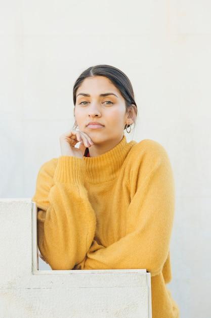 Portret van een mooie jonge vrouw kijken camera leunend op stappen Gratis Foto