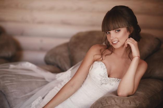 Portret van een mooie jonge vrouw. make-up en kapsel bij bruid. detailopname. bruiloft ochtend. zachte, tedere emotie op het gezicht Premium Foto