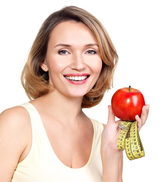 Portret van een mooie jonge vrouw met een meetlint en appel geïsoleerd op wit. Gratis Foto
