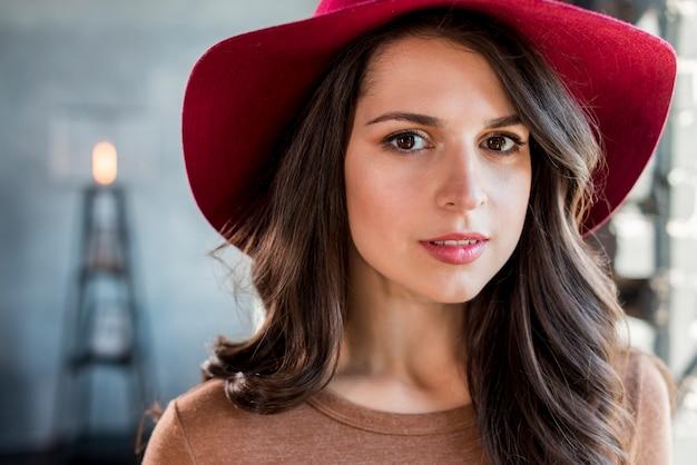 Portret van een mooie jonge vrouw met roze hoed op haar hoofd camera kijken Gratis Foto
