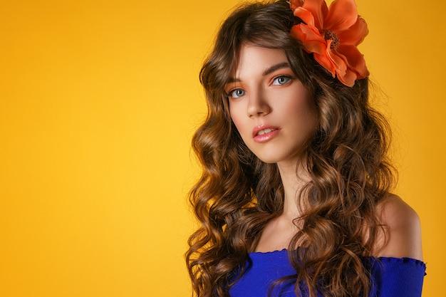 Portret van een mooie jonge vrouw op een gele achtergrond, Premium Foto