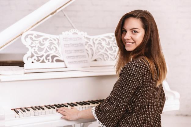 Portret van een mooie vrouw die de piano speelt Premium Foto