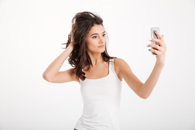 Portret van een mooie vrouw gekleed in tanktop die een selfie neemt Gratis Foto