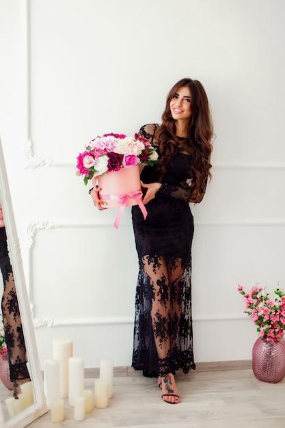 Portret van een mooie vrouw met een mand met bloemen Premium Foto