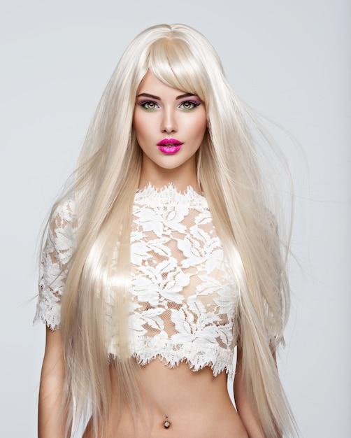 Portret van een mooie vrouw met lange witte rechte haren en lichte make-up. gezicht van een mannequin met roze lippenstift. mooi meisje poseren. Gratis Foto