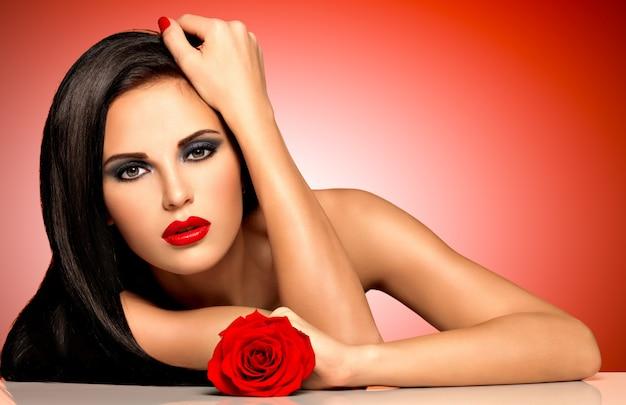 Portret van een mooie vrouw met rode lippen houdt de roos in de hand. mannequin met lonh haren poseren in studio op rode achtergrond Gratis Foto