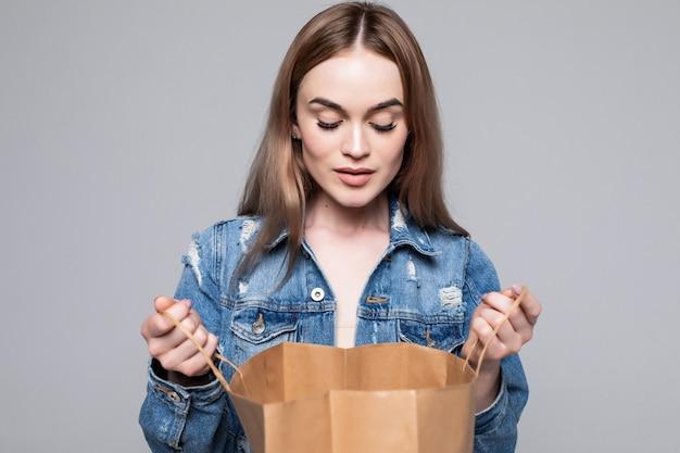 Portret van een nieuwsgierige jonge vrouw die binnen het winkelen zakken over grijze muur kijkt Gratis Foto