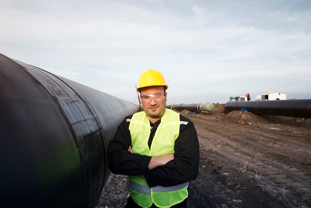 Portret van een olieveld werknemer permanent door gasleiding op bouwplaats Gratis Foto