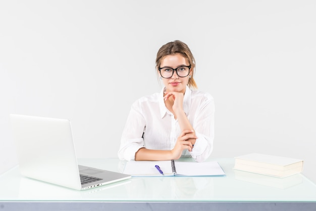 Portret van een onderneemsterzitting bij een bureau met laptop dat op witte achtergrond wordt geïsoleerd Gratis Foto