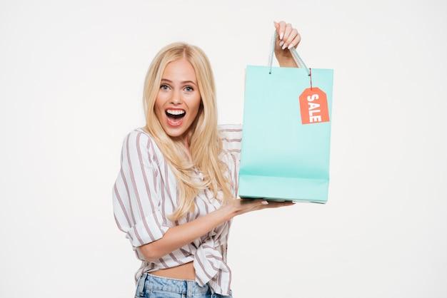 Portret van een opgewonden jonge de verkoop van de vrouwenholding het winkelen zak Gratis Foto