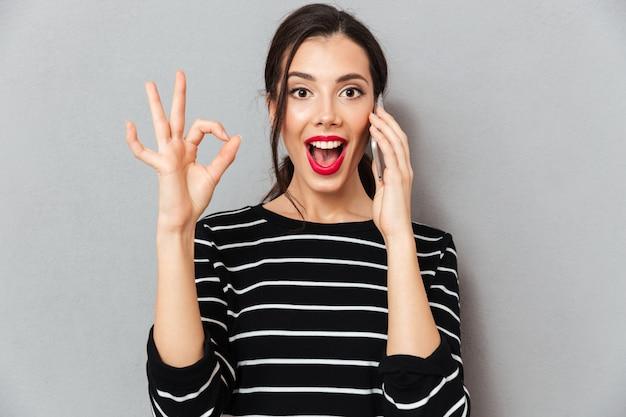 Portret van een opgewonden vrouw die op mobiele telefoon spreekt Gratis Foto