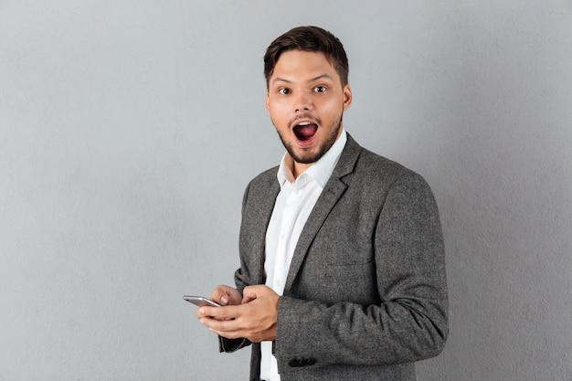 Portret van een opgewonden zakenman die mobiele telefoon houdt Gratis Foto