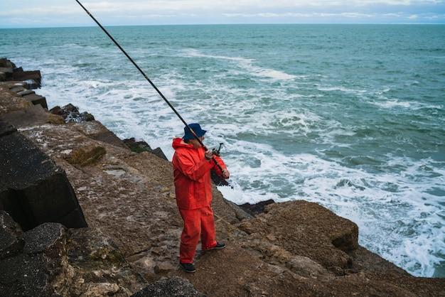 Portret van een oude man die in de zee vist. visserij concept. Gratis Foto