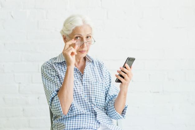 Portret van een oude smartphone van de vrouwenholding voor witte muur Gratis Foto