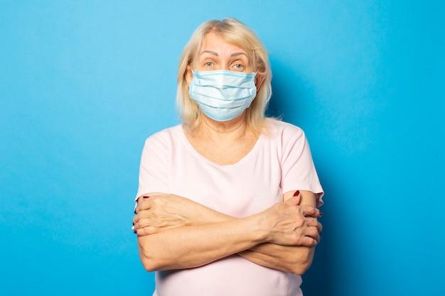 Portret van een oude vriendelijke vrouw in een t-shirt en een medisch beschermend masker sloeg haar armen over haar borst tegen een blauwe muur. emotioneel gezicht. conceptvirus, quarantaine, vuile lucht, pandemie Premium Foto