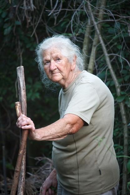Portret van een oude vrouw die met artritische voeten door het bos loopt dat op een stok als riet leunt Premium Foto