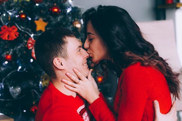 Portret van een paar verliefde mannen en vrouwen in rode truien bij de nieuwjaarsboom, een vrouw kust een man in de neus. Premium Foto