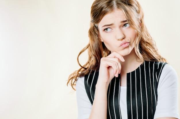 Portret van een peinzend en somber meisje op een lichte achtergrond, een sombere frons Premium Foto
