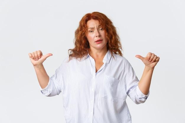 Portret van een pittige professionele vrouwelijke ondernemer, een roodharige vrouw van middelbare leeftijd die naar zichzelf wijst als een garantie dat ze elk probleem kan aanpakken. er zelfverzekerd uitzien, pronken over een witte muur. Premium Foto