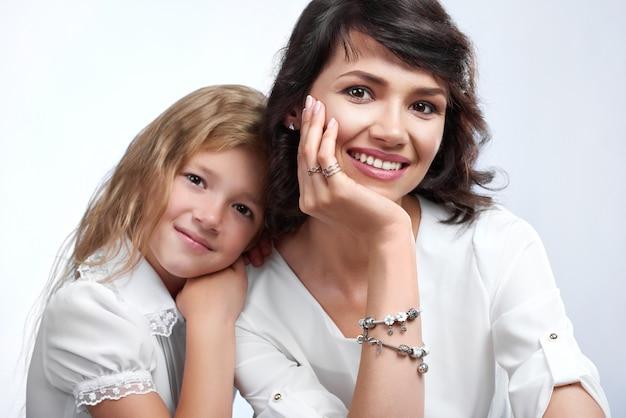 Portret van een prachtig gezinspaar: mooie moeder en haar dochtertje. ze zijn erg blij met een mooie glimlach. ze dragen witte t-shirts. Gratis Foto