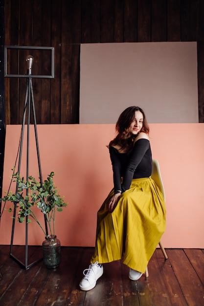 Portret van een prachtige modieuze vrouw, zittend in een stoel Gratis Foto