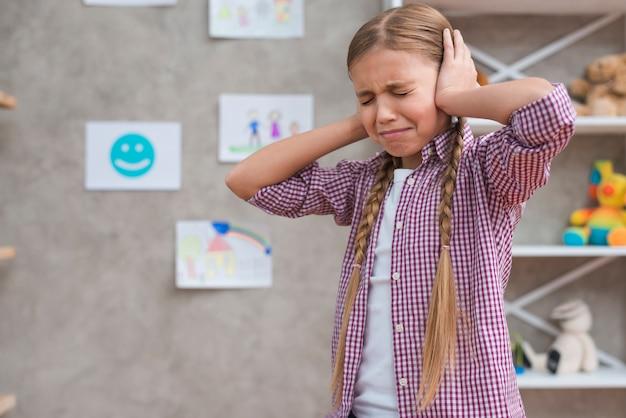 Portret van een radeloos meisje die haar oren behandelen met twee handen Gratis Foto