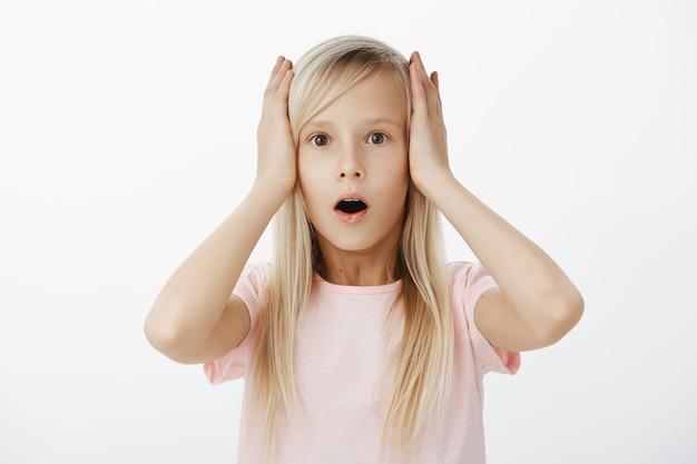 Portret van een schattig jong europees kind met blond haar in vrijetijdskleding, handen vasthoudend op het hoofd en kaak laten vallen van schrik en verbazing, staande verbijsterd over grijze muur Gratis Foto