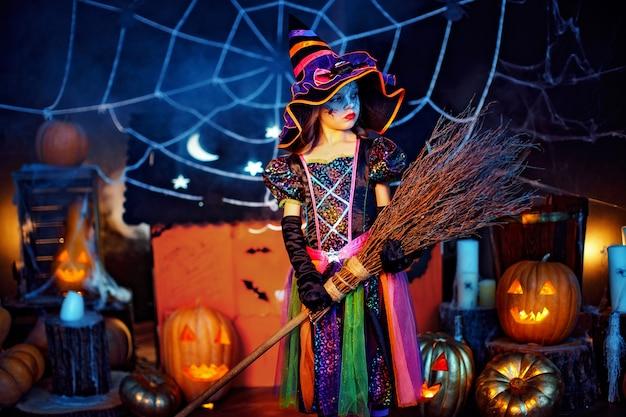 Portret van een schattig klein kindmeisje in een heksenkostuum met magische bezem. Premium Foto