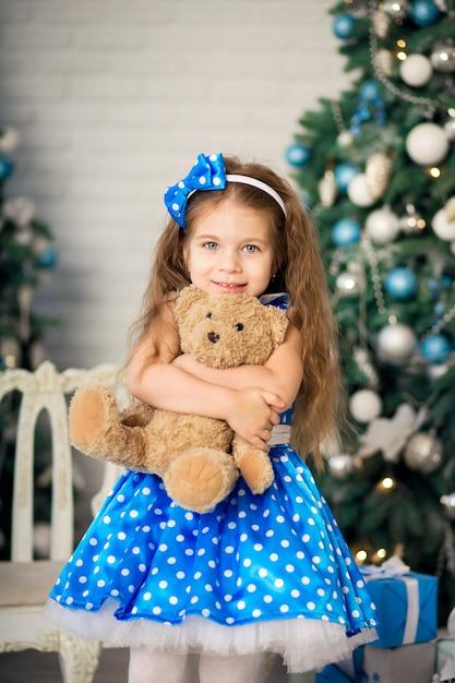 Portret van een schattig klein meisje in de buurt van een kerstboom. poserend met een teddybeer aan wie ze een kerstcadeau voor kerst kreeg aangeboden. Premium Foto