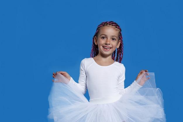 Portret van een schattig klein meisje in witte jurk dansen als een ballerina, over blauwe ruimte. ruimte voor tekst. Premium Foto