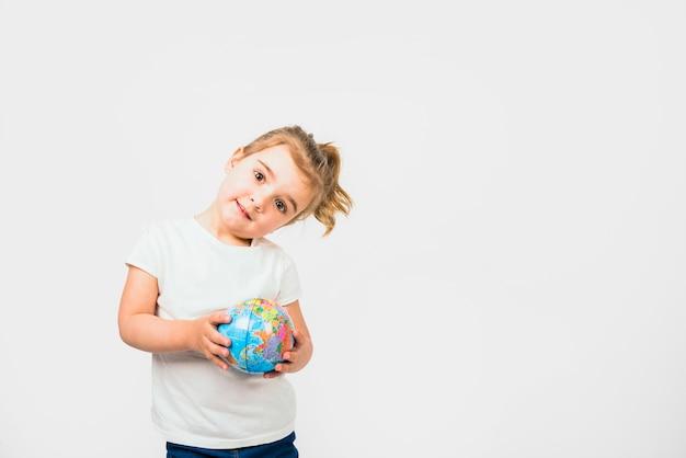 Portret van een schattig klein meisje met globe bal tegen een witte achtergrond Gratis Foto