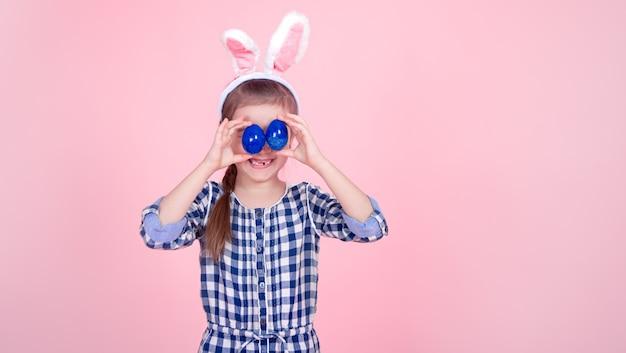 Portret van een schattig klein meisje met paaseieren op een roze achtergrond. Gratis Foto